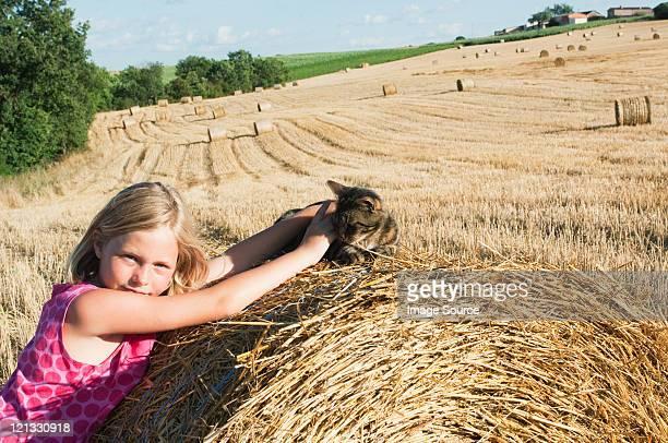 Mädchen mit einer Katze auf hay bale im Feld