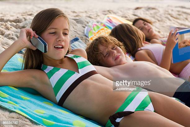 girl with cell phone on beach - swimwear stock photos and pictures