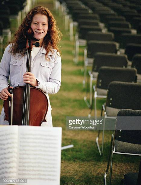 girl (10-12) with cello standing between rows of chairs, portrait - caroline roux photos photos et images de collection