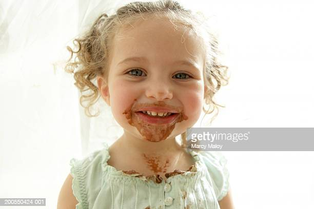 Girl (2-4) with chocolate ice cream on face, smiling, portrait
