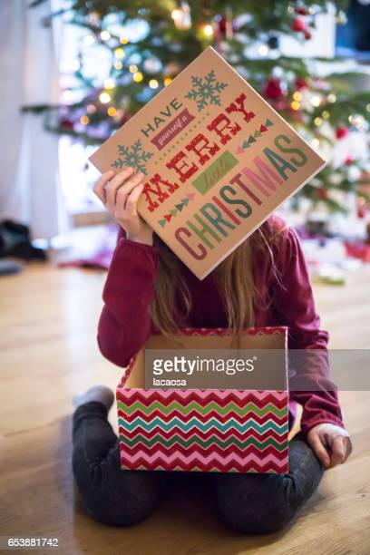 girl with christmas present in front of a christmas tree