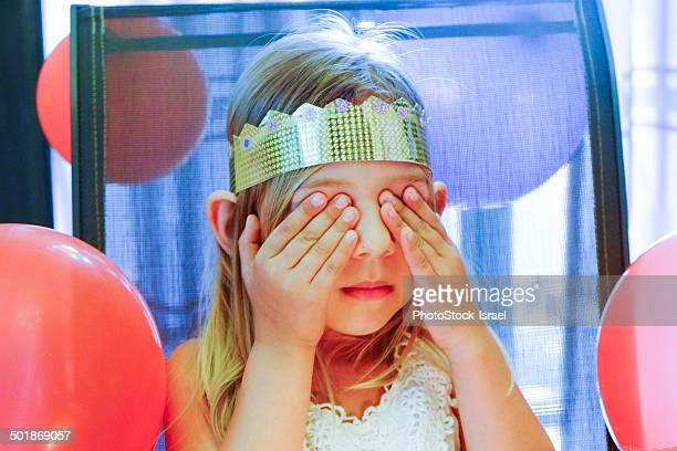 Girl with closed eyes making birthday wish