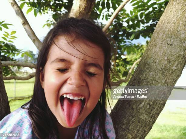 Girl With Closed Eyes Sticking Out Tongue Against Tree At Yard