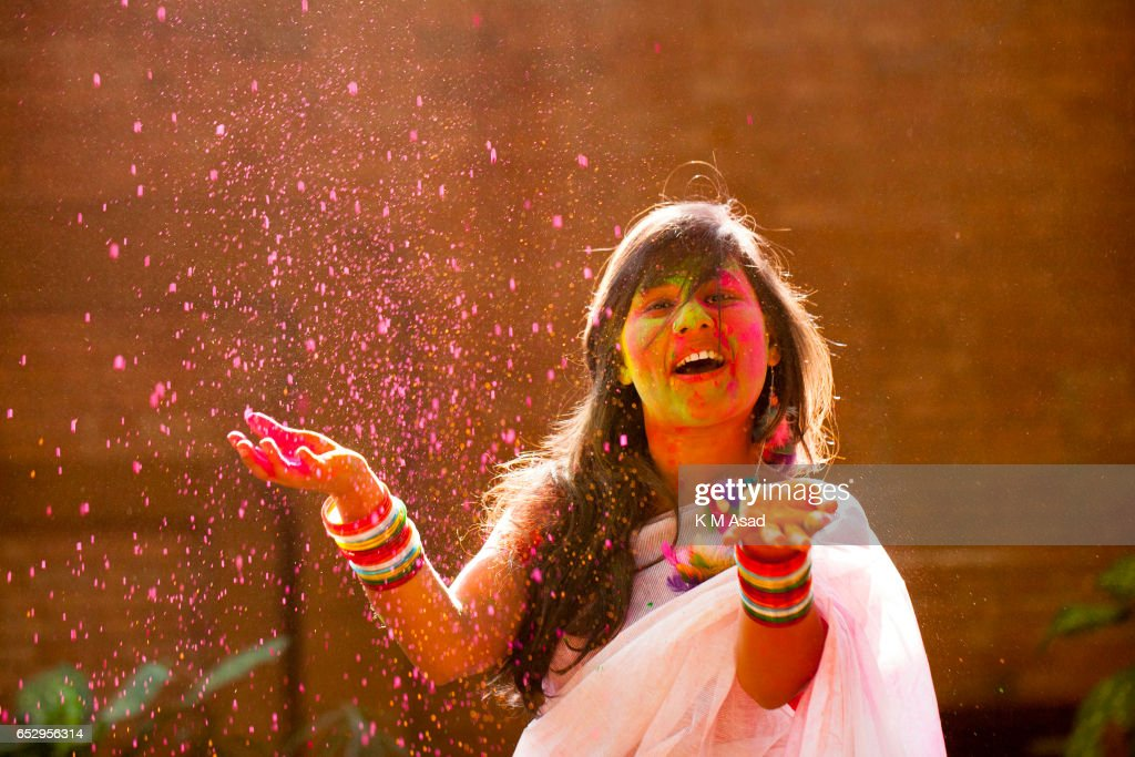 UNIVERCITY, DHAKA, BANGLADESH - : A girl with color powder attend celebrate the Holi Festival or Festival of Colors after smearing each other with colored powder in Dhaka, Bangladesh. Holi festival is celebrated on the full moon day in the month of Phalguna and marks the start of the spring season.