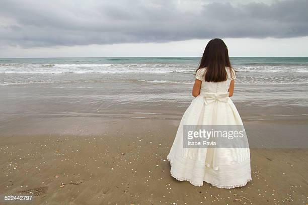 Girl with Communion dress at the beach