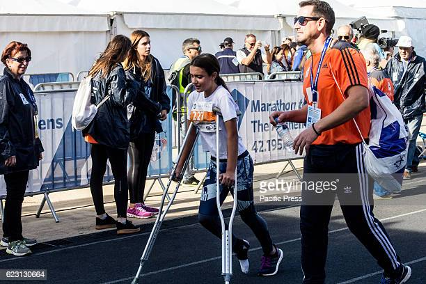 A girl with crutches finishes at the 5km race The 34st Athens Authentic Marathon marks the 120th anniversary of the first contemporary Marathon race...