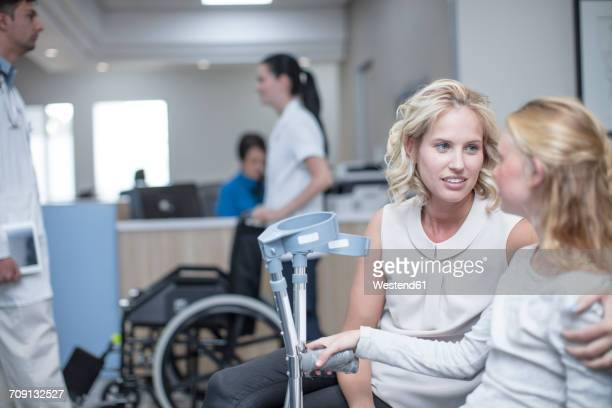 Girl with crutches sitting with her mother in reception area