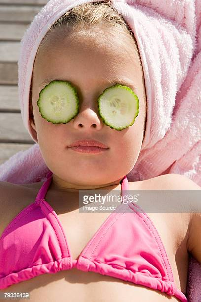 Girl with cucumber slices on her eyes