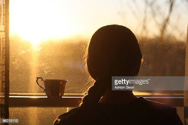 Girl with cup  at window