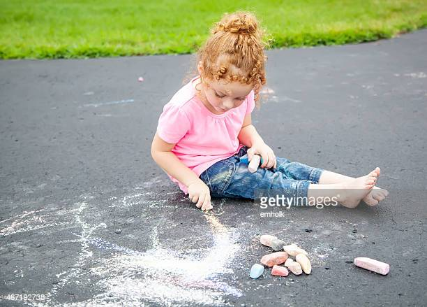Girl With Curly Red Hair Drawing With Chalk on Driveway