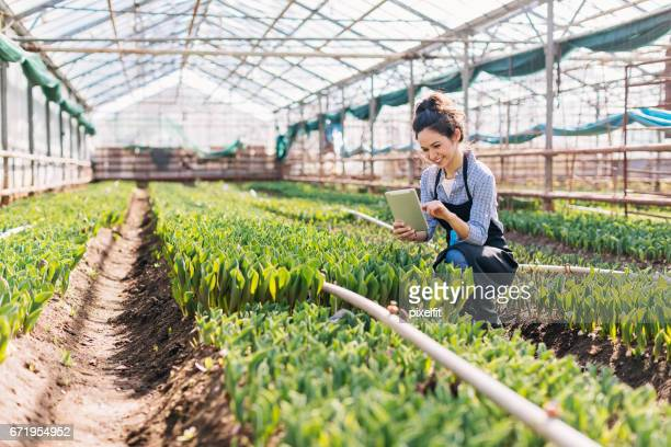 Girl with digital tablet working in a greenhouse