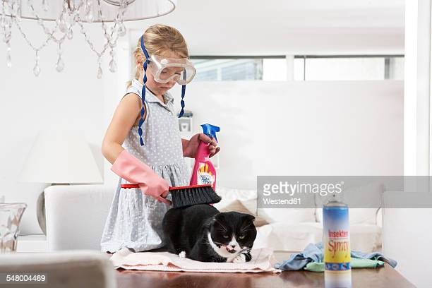 Girl with diving goggles cleaning cat on dining table