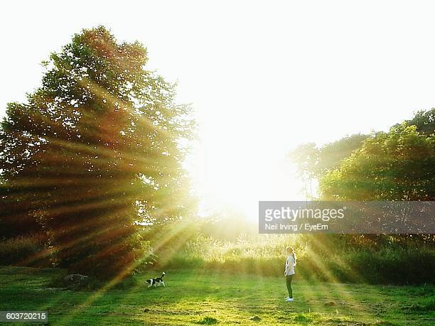 Girl With Dog On Grassy Field Against Bright Sky At Morning