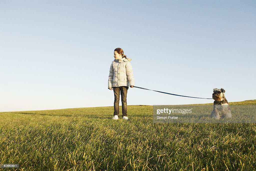 Girl with dog on lead, expanse of sky : Stock Photo