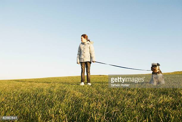 Girl with dog on lead, expanse of sky