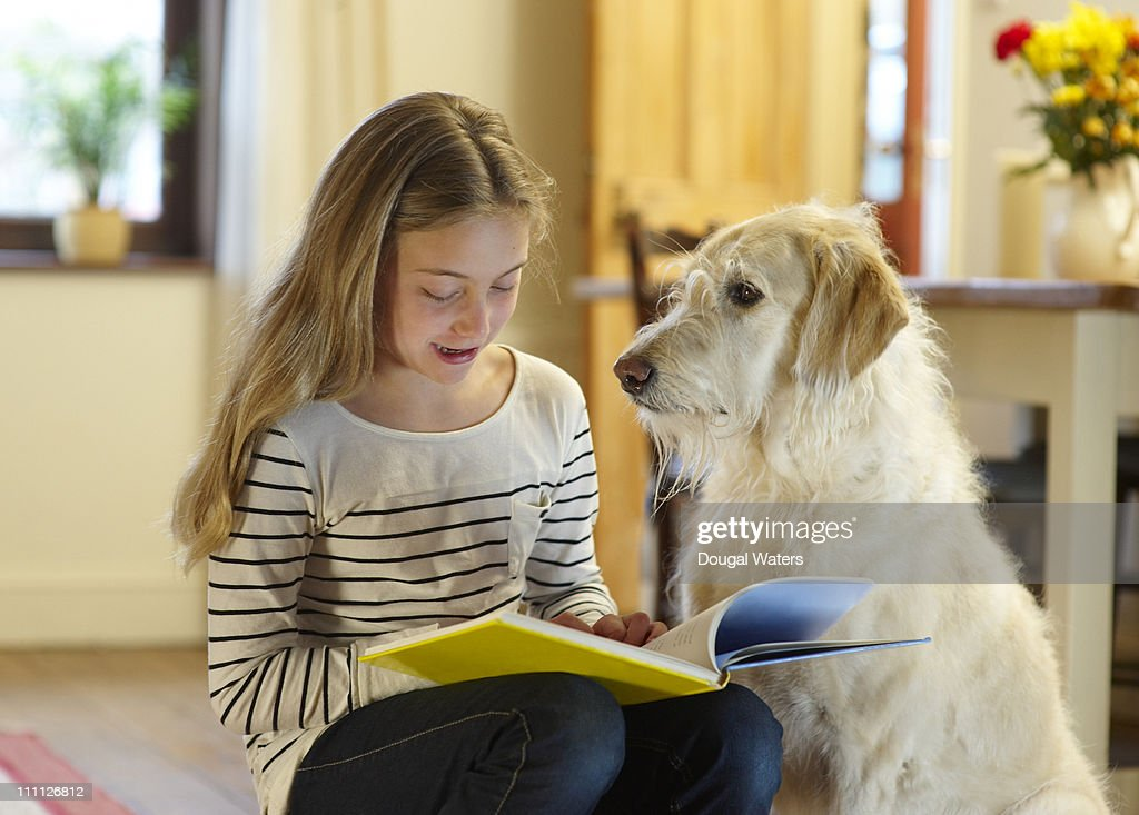 Girl with dog reading book. : Stock Photo