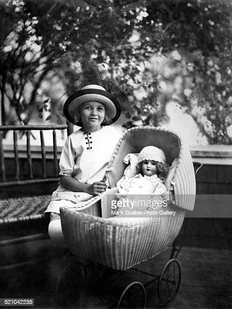 Girl with doll in baby buggy late 1910s