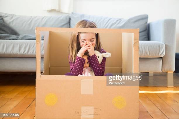 Girl with doll sitting in self-made cardboard car at home