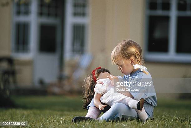 Girl (2-3) with doll sitting on grassland