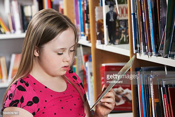 Girl (10-12) with Down syndrome holding book at bookshelves