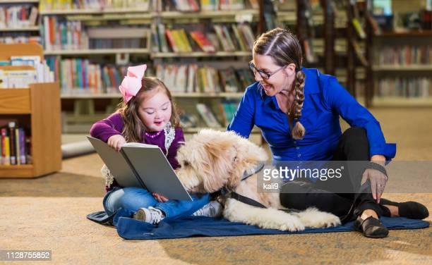 meisje met syndroom van down in bibliotheek met therapie hond. - disabilitycollection stockfoto's en -beelden