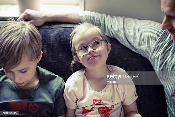 Girl with down syndrome looking at father by brother on sofa