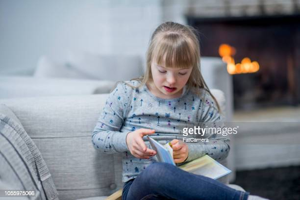 Girl with down syndrome reading a book at home