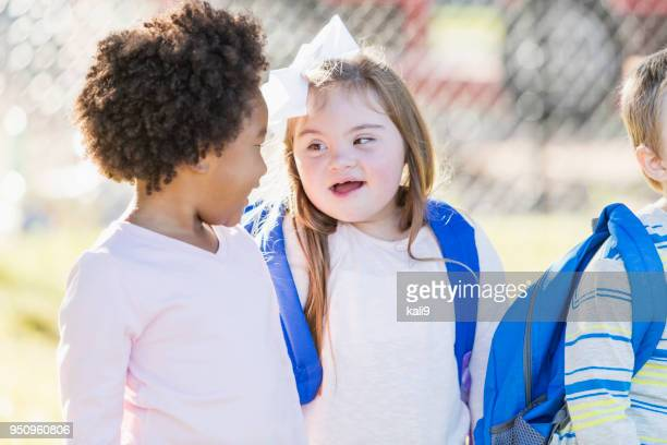 girl with down syndrome talking to friend in schoolyard - preschool student stock pictures, royalty-free photos & images