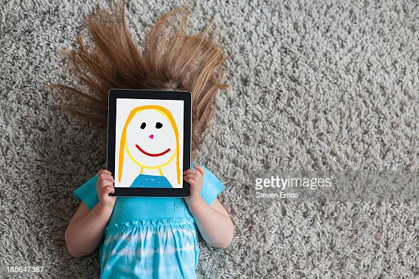 girl with drawn self-portrait on a digital tablet - obscured face stock pictures, royalty-free photos & images