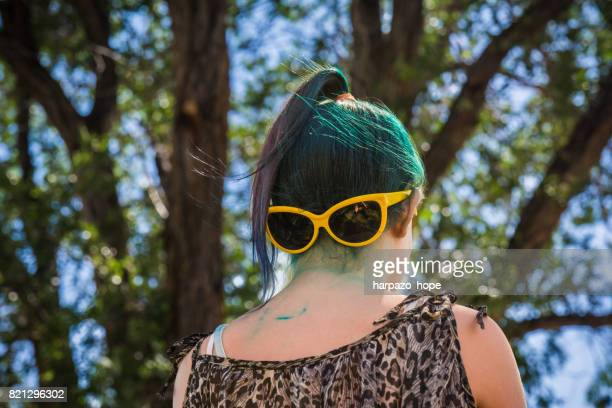 Girl with dyed hair and stained neck wearing her sunglasses backwards.
