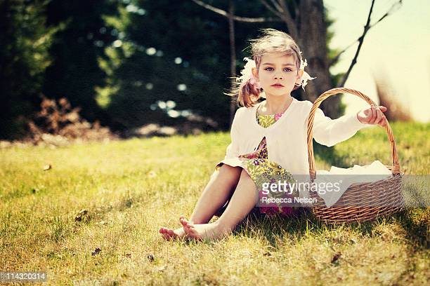 Girl with Easter basket sitting on a hill