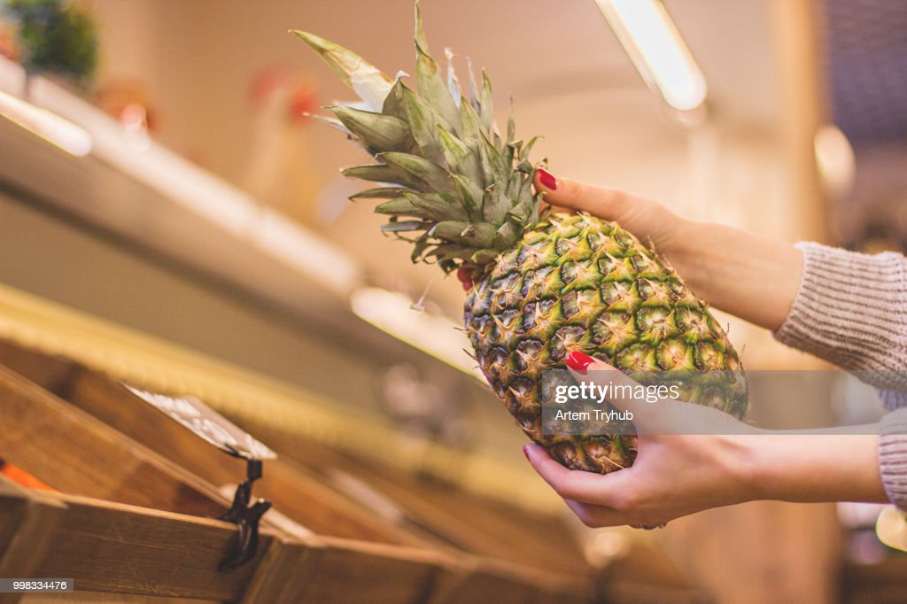 Girl with exotic pineapple in hands at supermarket : Stock Photo