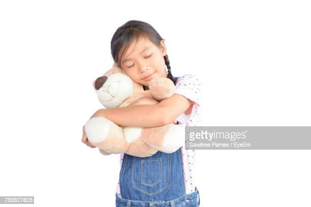 Girl With Eyes Closed Embracing Teddy Bear While Standing Against White Background