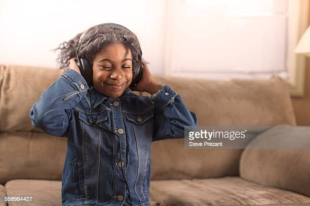 Girl with eyes closed listening to headphone music on sofa