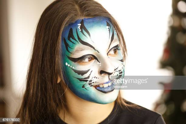 Girl with face painted in front of Christmas tree