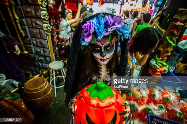Girl with fantasy and catrina makeup shakes up transeuentes and consumers at Ladeira Porto Geral on 31 October 2018 in Sao Paulo, Brazil. La Catrina...