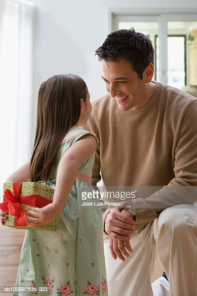 Girl (4-5) with father, girl hiding present behind back