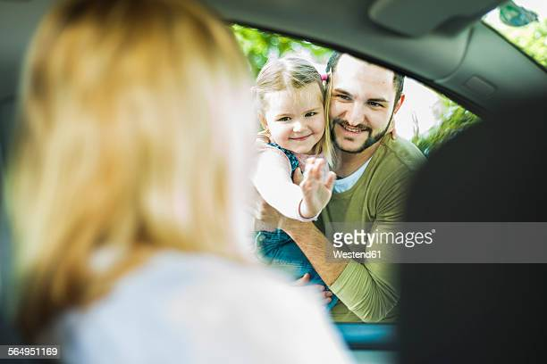 Girl with father saying goodbye to leaving mother in car
