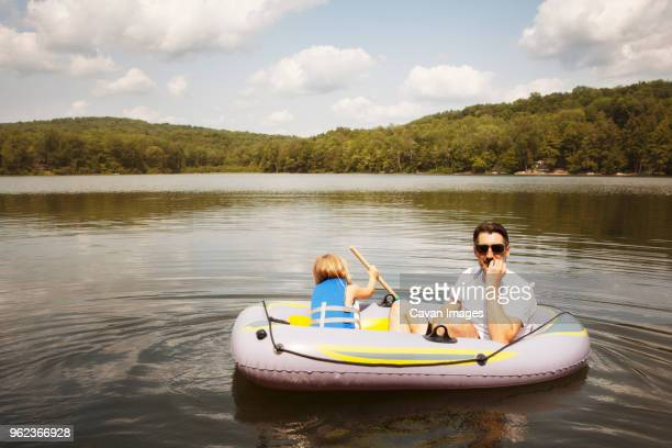 Girl with father sitting in inflatable raft