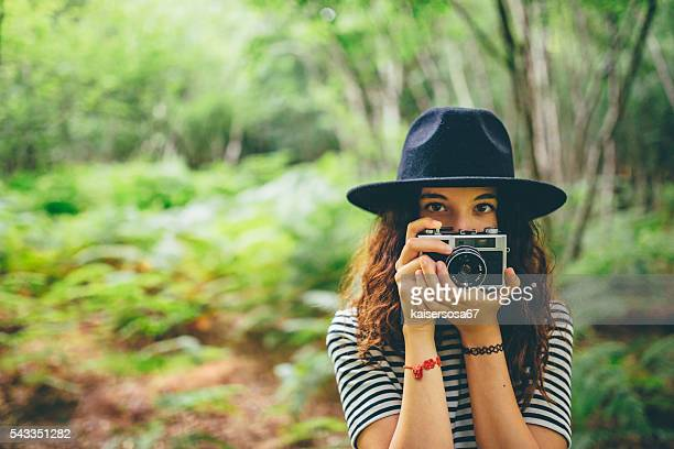 girl with film camera taking photo in the forest - photographic film camera stock photos and pictures