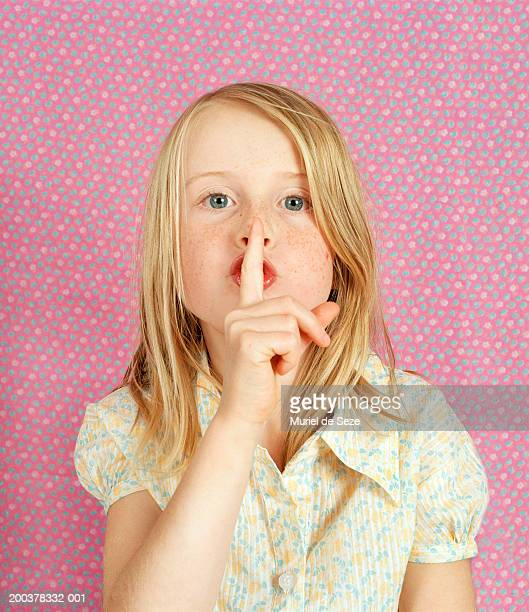 Girl (6-8) with finger by mouth, portrait