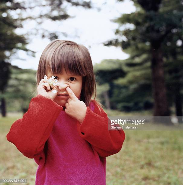 Girl (4-6) with finger in nose, and holding flower, portrait