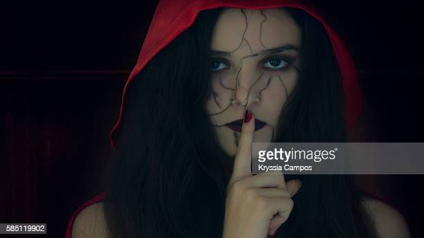 girl with finger on lips and a painted face for halloween - zombie makeup stock photos and pictures
