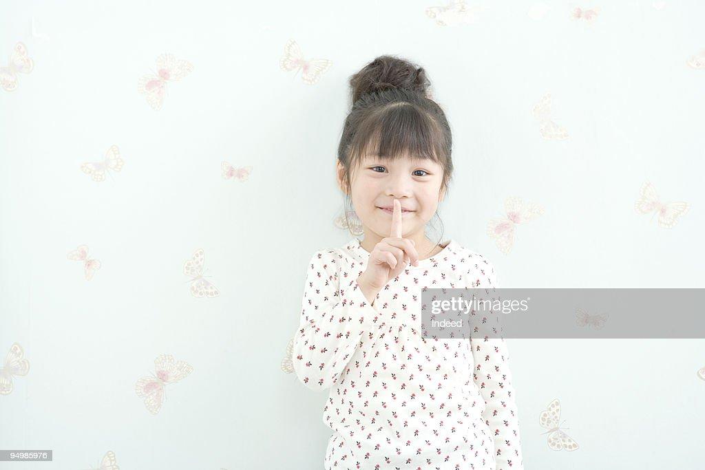 Girl (4-6) with finger to lips shushing  : Stock Photo