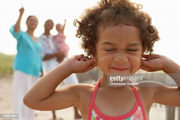 girl (3-4) with fingers in ears, head and shoulders, with family behind - fingers in ears stock pictures, royalty-free photos & images