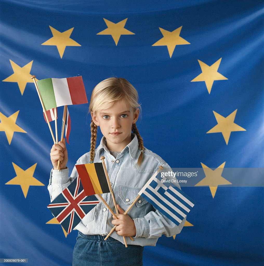 Girl (8-9) with flags of various countries standing against European Union flag : Stock Photo