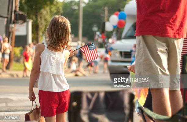 girl with flags watches 4th of july parade in america - parade stock pictures, royalty-free photos & images