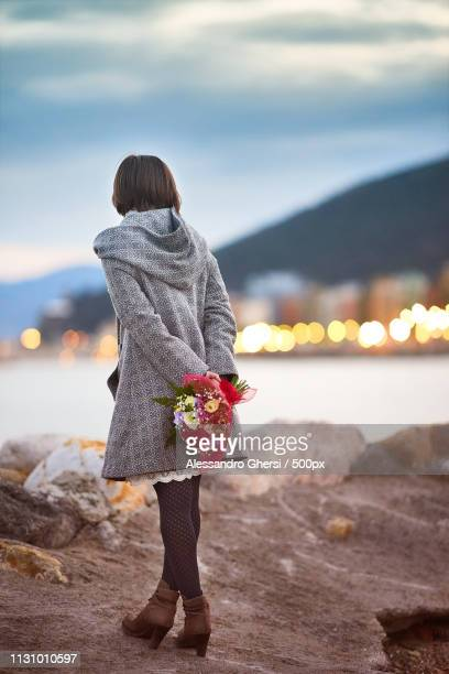 Girl With Flowers On A Cliff Overlooking The Sea
