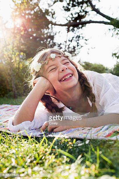 Girl with flowers round head laughing with eyes closed