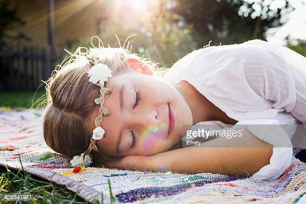 Girl with flowers round head sleeping